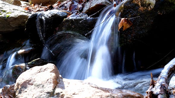 Water passes across rocks in a stream crossed by Jones