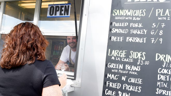 Trevor Gardner talks with a customer after handing her food to her as he works inside the Valley Pike BBQ Co. food truck which is set up at Lee Highway and Fadley Road in Weyers Cave on Tuesday, May 12, 2015. Gardner and his father are hoping to get a farmers market and food truck park operating at the location.