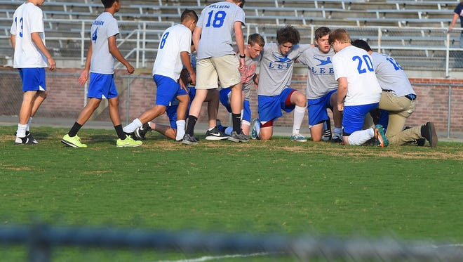 Their game postponed, Robert E. Lee boys' soccer team gathers center of their home field following the girl's game. They wanted a moment of silence in honor of a player from East Rockingham High School, the team they were to play, who was killed in a wreck early that day on Friday, May 22, 2015.