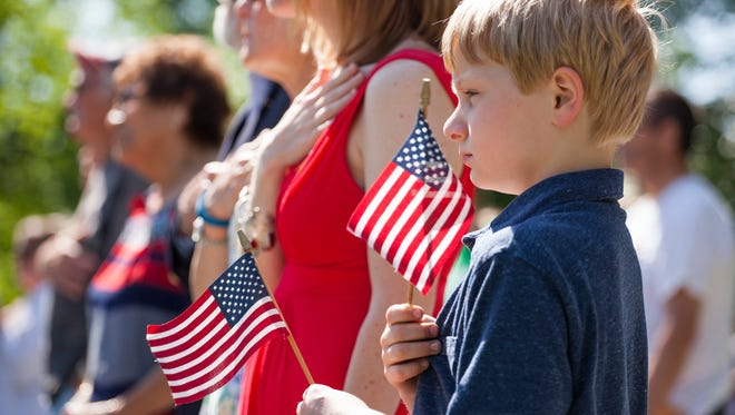 Nathan Sprouse, 8, of Fishersville, waves American flags as members of Robert E. Lee High School's choir sing the National Anthem during a Memorial Day ceremony at Gypsy Hill Park on Monday, May 25, 2015.