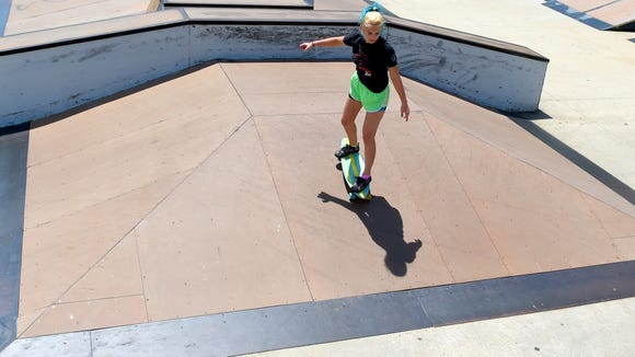 Madie Shifflett, 13, of Fishersville casts a shadow as she rolls down one of the ramps at the skate park.