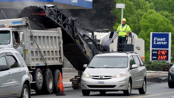 """Corey Phillips of Slurry Pavers Inc. operates a milling machine along Greenville Avenue in Staunton on Tuesday, June 2, 2015.  """"This machine just takes up the old pavement, so when they can just come back and lay the asphalt over the old stone,"""" said Phillips.  Crews worked to break up the existing pavement along the section of road between Richmond Road and Statler Boulevard so that it can be paved."""
