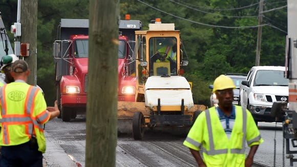 In the wake of the milling machine, the roadway is scraped to remove access bits of pavement left behind.