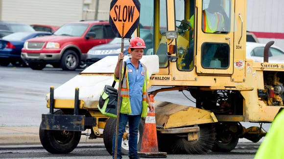 Carol Hensley of B & S Contracting Inc holds a sign controlling the flow of traffic as crews work to breakup and remove the existing pavement on Greenville Avenue.