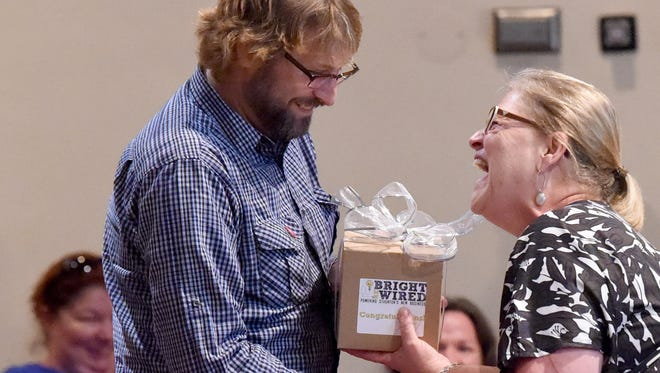 Wavley Groves of EccoHollow Art and Sound shares a laugh with Executive Director Julie Markowitz of the Staunton Downtown Development Association as he wins $10,000 through the Bright ReWired business plan competition in 2015.