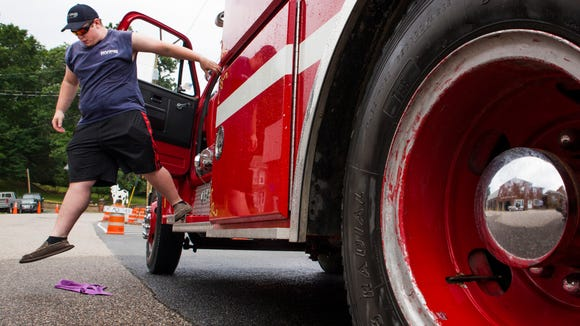 Jordan Taylor, second lieutenant at Raphine Volunteer Fire Company, steps off a tanker truck while cleaning it in preparation for the evening's parade on Friday, June 19, 2015.