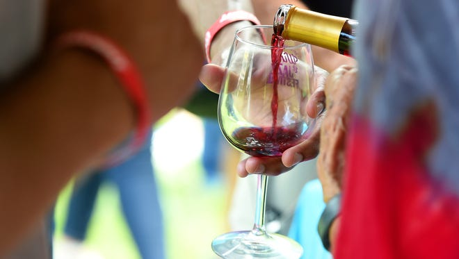 A sample of wine is poured into the glass of a festival goer at the tent for Blue Ridge Vineyard.