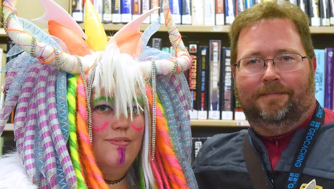 Wearing a dragon costume of her own design, cosplayed Amy Tripp is is photographed with photographer Mike Tripp, also her father, who wears a Starfleet uniform from the Star Trek universe. Amy served as one of the judges of the costume contest for the event while Mike photographed the event for the News Leader.