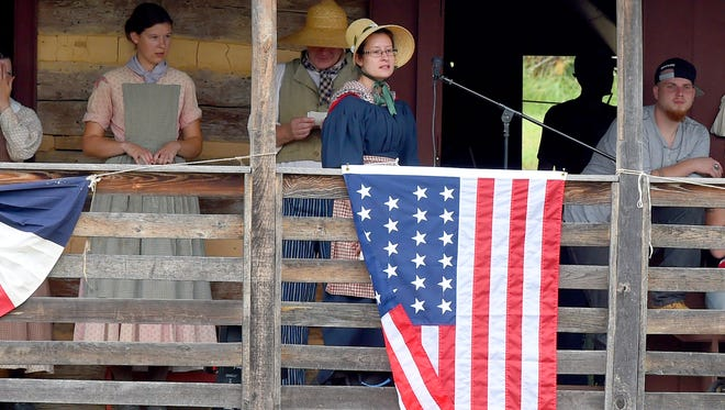 News Leader reporter Megan William steps up and recites a toast from 1814 during a ceremony on the 1820s American Farm following the reading of the Declaration of Independence. Dressed in traditional clothing common to the 1800s, she chose to volunteer for a day at the Frontier Culture Museum, to see what itÕs like for the costumed historic interpreters, during their annual Fourth of July celebration on Saturday, July 4th, 2015.