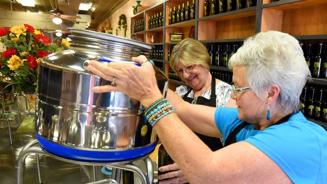 Jenny Gallaugher and MaryEllen Parry work together to pour the last bit of one of the flavors of olive oil into a bottle for a customer while working at Staunton Olive Oil Company in downtown Staunton on Thursday, July 9, 2015.