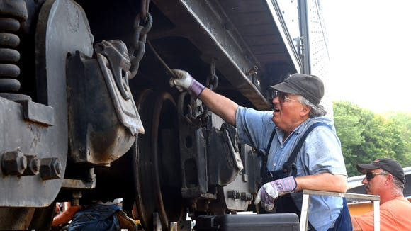 Dennis Daughtery  helps secure the tenders for steam locomotives 1238 and 1286 onto railcars.