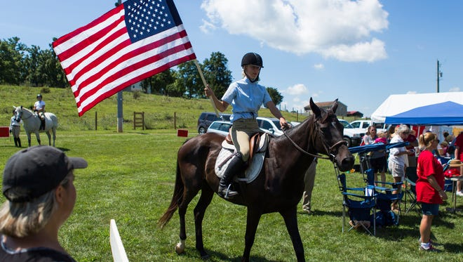 A rider carries the American Flag into the ring during the 58th annual Middlebrook Horse Show on Saturday, August 1, 2015.