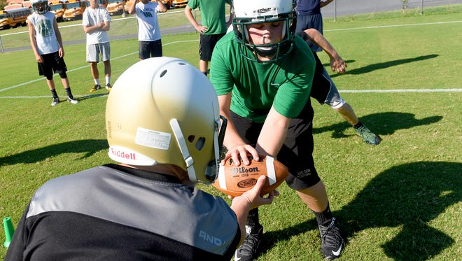 Bryce Humphreys, 14, receives the ball during drills on the first day of team football practice at Wilson Memorial High School on Monday, August 3, 2015.