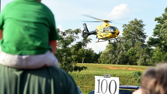 Children and adults watch as PHI Air Medical's Aircare 5 helicopter comes in for a landing.