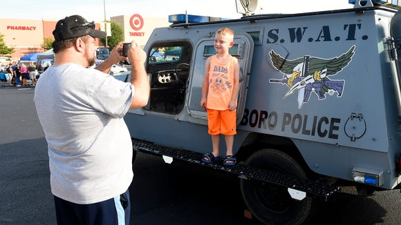 Dana Dixon, 7, of West Virginia stands proudly on the side of a Waynesboro Police SWAT vehicle as his grandfather, Ron Ward of Staunton, takes his photograph. They attend the 32nd National Night Out held at the Waynesboro Town Center on Tuesday, August 4, 2015.