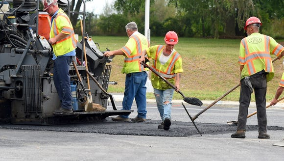 A work crew conducts paving operations at Lifecore