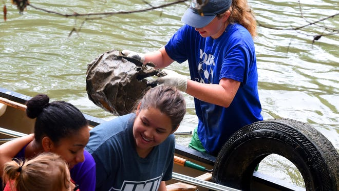 James Madison University student Aubrey Siebels carries an old fuel can just pulled out of the Middle River and puts it in the canoe. Friends of the Middle River held its annual Middle River Cleanup Day on Saturday, Sept. 12, 2015.