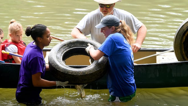 James Madison University students Jesmine Roberts-Torres and Aubrey Siebels, lift a tire pulled from the Middle River to place it in a waiting canoe with help from Neil Tucker of Fort Defiance. Friends of the Middle River held its annual Middle River Cleanup Day on Saturday, Sept. 12, 2015.