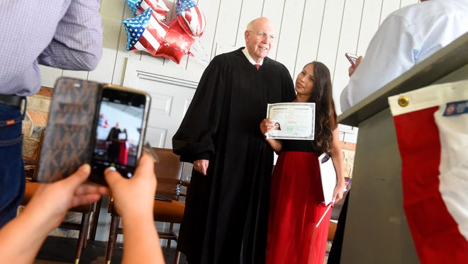 Judge James G. Welsh is photographed with newly naturalized U.S. citizen Rossy Yessenia Garcia following the naturalization ceremony he presided over at the Frontier Culture Museum on Tuesday, Sept. 15, 2015. The ceremony marked the 60th one Welsh has presided over, with him having watch as more than 3,000 petitioners in those ceremonies became U.S. citizens. Welsh retires in 14 days