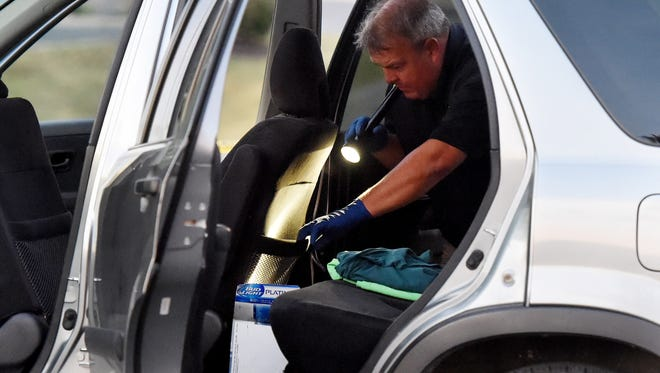 Special agent Vince Fielding of the Virginia State Police's Bureau of Criminal Investigation searches the inside of a Honda CR-V for more evidence as part of a criminal investigation in the parking lot in Staunton on Wednesday, Sept. 16, 2015. After being stopped, the Honda driver shot himself in front of a Virginia State Police trooper shortly before 12:30 p.m., according to Corinne Geller, a state police spokesperson.