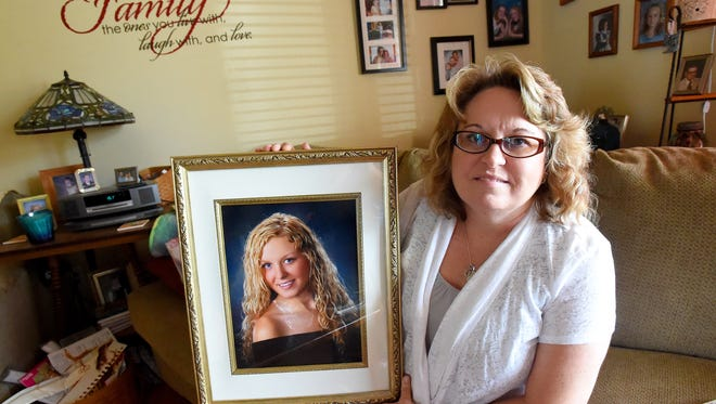Kim Sours holds up a photo of her daughter, Keri Carter, in her residence near Stuarts Draft on Thursday, Sept. 24, 2o15. Kim still feels the loss of her daughter, who committed suicide in 2013. A suicide prevention walk is being held at Gypsy Hill Park on Oct. 10.