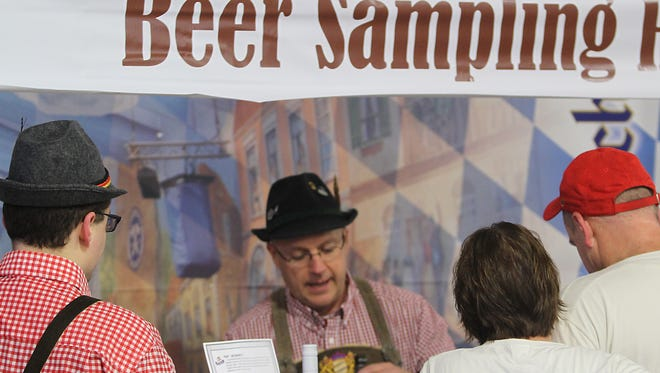 Lee Reiherzer mans up the beer sampling booth at the Fifth Annual Oktoberfest in Oshkosh Saturday.