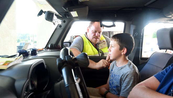 Thomas Ratcliffe of Augusta Health administers a flu vaccination to Brady Ward, 13, outside the Augusta Health Urgent Care Center in Waynesboro on Thursday, Oct. 8, 2015. The Virginia Department of HealthÕs Central Shenandoah Health District teamed up with Waynesboro Emergency Management and Augusta Health to provide a free drive-thru flu vaccination clinic as a test of their emergency dispensing plans.