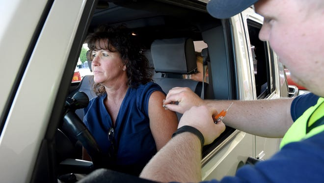 From the comfort of her vehicle, April Ward looks forward as volunteer Chris Kichinko prepares to administer a flu vaccination outside the Augusta Health Urgent Care Center in Waynesboro on Thursday, Oct. 8, 2015. The Virginia Department of HealthÕs Central Shenandoah Health District teamed up with Waynesboro Emergency Management and Augusta Health to provide a free drive-thru flu vaccination clinic as a test of their emergency dispensing plans.