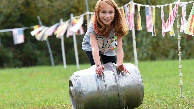Kaileigh Atkinson, 10, of Fishersville rolls her barrel down a straightway while participating in a barrel race during Oktoberfest at the Frontier Culture Museum on Saturday, Oct. 24, 2015.