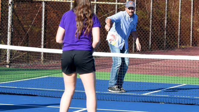 Recreation manager James Corbett returns the ball as intern Madison Westmoreland watches during a game of pickleball. Four members of the Staunton Parks and Recreation staff came together on the courts to learn the sport  at the new pickleball courts at Montgomery Hall Park on Wednesday, Oct. 21, 2015.