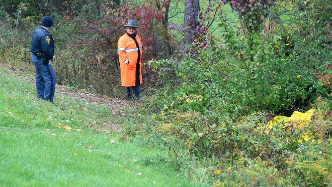 Virginia State Police remain on the scene of where a body was discovered alongside a path between Frontier Ridge Apartments and Walmart in Staunton on Tuesday, Oct. 27, 2015.