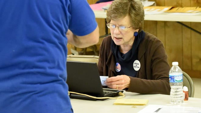 Officer of Election Linda Shifflett checks-in an arriving voting at the Weyers Cave voting precinct on Tuesday, Nov. 3, 2015.