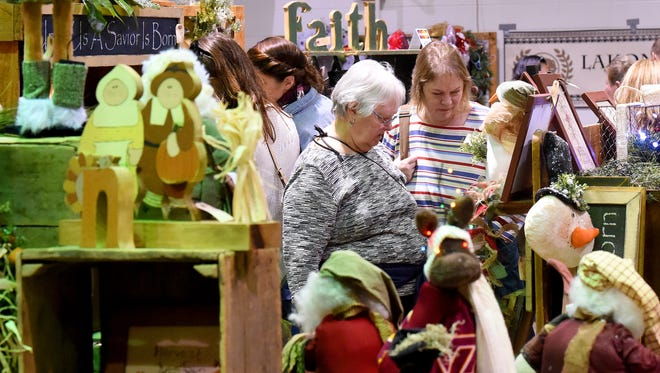 Christene Houseknecht of Greenville and DeAnn Houseknecht of Churchville brows one of the many vendor booths at the Fall Art and Craft Show held at Augusta Expo in Fishersville on Saturday, Nov. 14, 2015. The event continues Sunday.