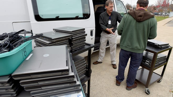 Technology support technician Allen Daughtrey takes an armload of computers from co-worker Alan Kite before passing them into the van. They work to retrieve approximately 250 older laptops from Bessie Weller Elementary on Tuesday, Nov. 17, 2015. Recently replaced, with Chromebooks, iPads and laptops as part of a technology initiative, plans are to have the older model computers collected from the various elementary schools rehabbed and give to families that donÕt have computers at home so students can have access in and outside of the classroom.