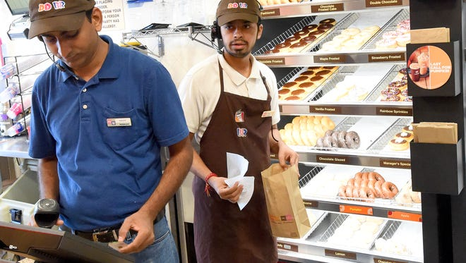Crew member Yanis Patel retrieves the donuts for a customer as owner Sandip Patel works the register at the Dunkin Donuts located on Richmond Ave in Staunton on Thursday, Nov. 19, 2015.  The business recently reopened following renovations.