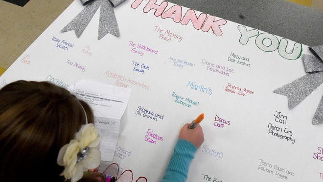 Eighth-grader Kirsten Hildebrand works on a thank you poster listing event sponsors. Members of the FCCLA assist with making decorations for an upcoming Breakfast for Santa following school at Wilson Middle School on Monday, Nov. 23, 2015. Scheduled for December 12, the event will be held by the schoolÕs FCCLA at Bridge Church in Fishersville and serves as a benefit for Brayden Kier and Aubrey Gutshall-McCray.