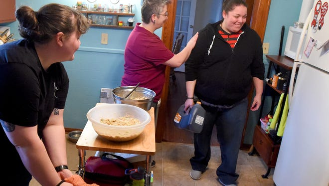 Nancy Gaston (center) welcomes Searcy Hughes who arrives with the tea as Amanda Francis looks towards the latest arrival. A Friendsgiving dinner is prepared at a home in Staunton on Thanksgiving afternoon, Nov. 26, 2015.