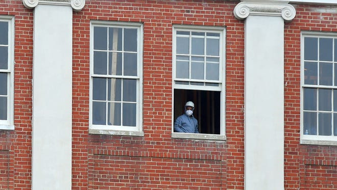 Hard hat and mask in place, a worker looks out from an upper floor window of a building currently being renovated at the Villages at Staunton on Monday, Dec. 14, 2015.
