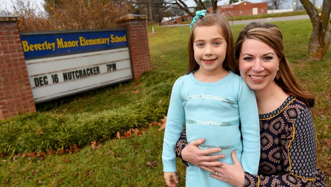 Katie Ballew has her arms around daughter Gracie, a second-grader at Beverley Manor Elementary, next to the school's sign on Monday, Dec. 14, 2015. Katie was involved with a petition asking Eric Bond, superintendent of Augusta County Schools, to lock down the front entrances of all the county's school buildings.