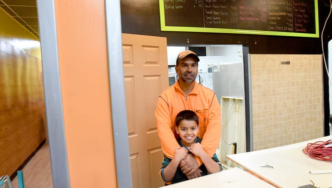 Ranjit Rana, owner Stevie G's Gluten Free Bakery, has his arms around his son, Vinnie Rana, 8, as they stand inside the space being renovated for his business in downtown Waynesboro on Monday, Dec. 21, 2015.
