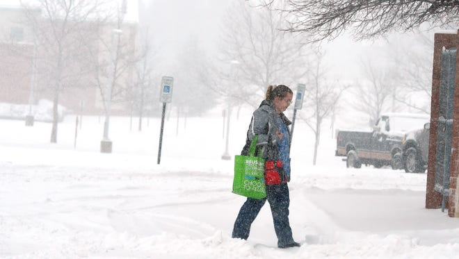 A lady crosses a snow covered parking lot at Augusta Health during a snow storm in Fishersville on Friday, Jan. 22, 2016.