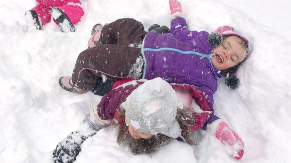 Kayla Cypher, 4, has fun falling on top of her 6-year-old sister, Chloe Cypher, as they play in the snow in Staunton as a winter storm enters its second day on Saturday, Jan. 23, 2016.