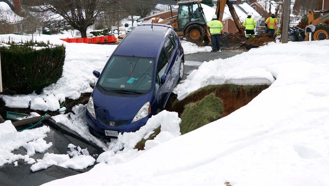 A Honda Fit is balanced on the edge of a sinkhole that opened up under the driveway of a residence on Skymont Road as Staunton Public Works repair a broken waterline across the road on Tuesday, Jan. 26, 2016.