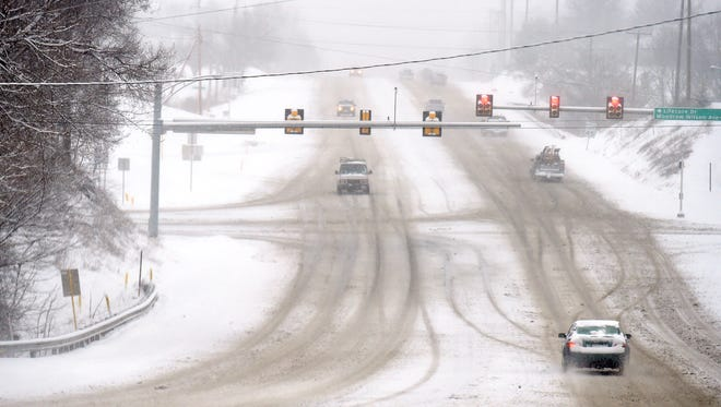 Snow continues to fall as traffic moves slowly along U.S. 250 in Fishersville as a winter storm passes through the area on Monday, Feb. 15, 2016.