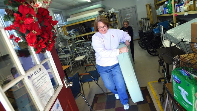 Volunteer coordinator Regina Griffin helps carry the mattress of a newly donated medical bed outside of the shop for the Health Equipment Loan Program, aka. HELP, with the help of volunteer Jean Liggett in Churchville on Thursday, Feb. 18, 2016.