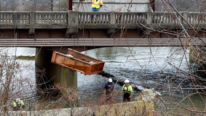 A crane uses a metal bin to lower sandbags down to workers building a coffer dam in the South River around piers of the Main Street bridge in Waynesboro on Monday, Feb. 22, 2016. Coffer dams creates a semi-dry space for crews to work while helping prevent any impacts to the waterway as demolition of the bridge begins.