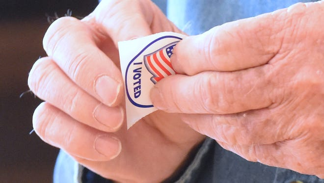 """A resident of Augusta County, Meredith Moran of Staunton peels his """"I Voted"""" sticker off its backing to stick it on his shirt after voting at the Middlebrook precinct during the primary elections on Tuesday, March 1, 2016."""