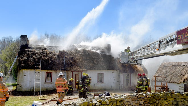 Firefighters work to control a fire that started in the thatch roof of the 1700s Irish Farm at the Frontier Culture Museum on Tuesday, April 5, 2016.