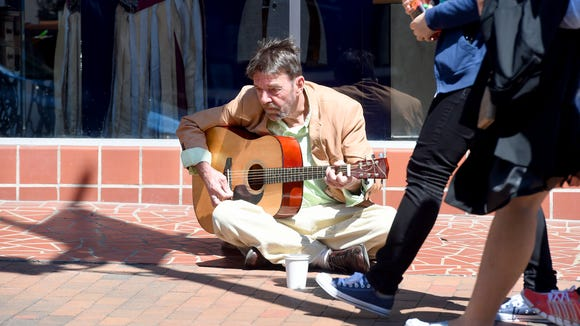 "Sitting in the sunlight, Linwood McCloud strums the guitar. He sings ""Jimmy Brown the Newsboy,"" his favorite being country music, while sitting at a vacant storefront on East Beverley Street in downtown Staunton on Thursday, April 14, 2016."