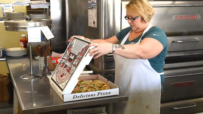 Owner Pam Powers boxes up a pizza fresh from the oven at Ma and Pa's Pizza near Terry Court in Staunton on Friday, April 29, 2016. The establishment closes its doors after their Friday night's dinner service.